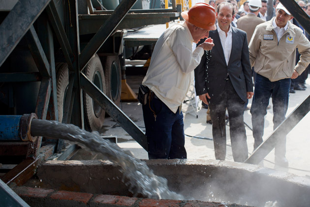 Mexico City's mayor and general director of the country's National Water Commission watch as a geologist takes a drink of water from an exploratory well into an aquifer underneath Mexico City, on Jan. 23, 2013. (Dario Lopez-Mills/AP Photo)
